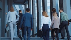 Group of friendly colleagues metting on the street before working day. Confident caucasian boss leading his successful team staff workers to corporate building.