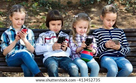 Group of friendly smiling children posing at urban street with mobile devices