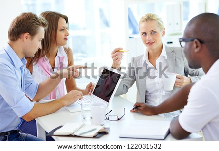 Group of friendly students or businesspeople having meeting