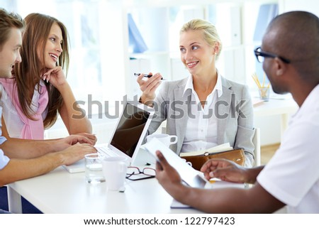 Group of friendly students or businesspeople interacting in office