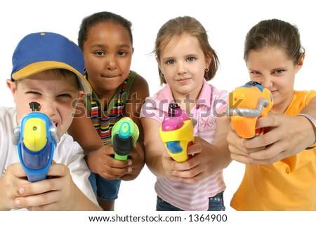 Group of friends aiming water guns at camera.