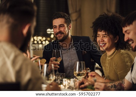 Group of friends are enjoying a meal in a restaurant. They are are talking and laughing while eating and drinking wine.
