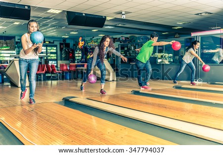 Group of friends at bowling - Young people having fun at bowling, four players throwing balls on the bowling track
