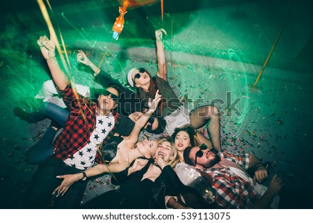 Group of friends at club lying on the floor and having fun. New year's party
