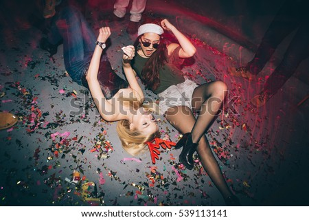 Group of friends at club lying on the floor and having fun. New year
