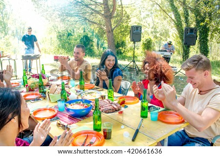 group of friends at garden barbeque lunch smiling at colorful lunch table while cooking at the smoking barbecue grill in sunny park background - weekend get-together lunch with family friends