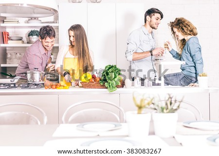 Group of friends at home party, woman cooking dinner for her guests - Young adults talking and having fun at home while preparing a delicious meal