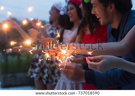 Group of friends at rooftop bar having fun sparklers in the party celebration. #737018590