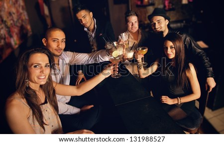 Group of friends at the bar raising their glass for a toast