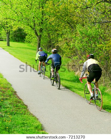 Group of friends bicycling in a summer park