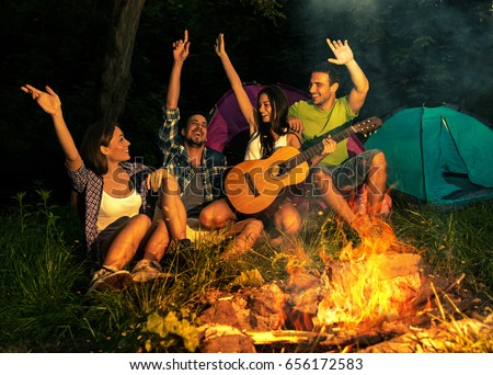 Group of friends camping.They are sitting around  camp fire, playing guitar and roasted sausages.
