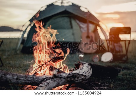 Photo of  Group of friends camping.They are sitting around fire camp.