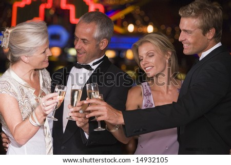 Group of friends celebrating in casino with champagne
