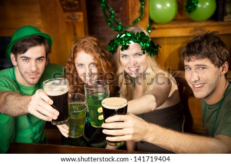 Group of friends celebrating St. Patrick's Day at a pub.