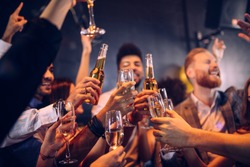 Group of friends cheering with champagne and beer