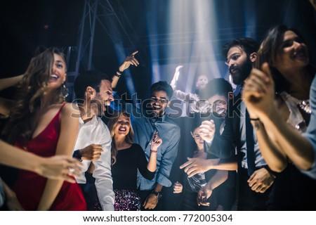 Group of friends dancing in the nightclub