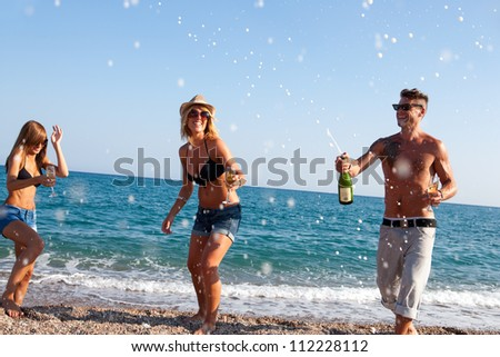 Group of friends dancing under champagne bubbles on beach.