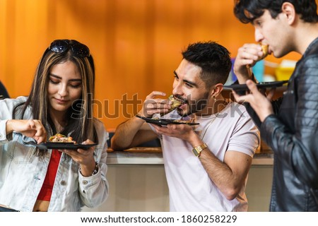 group of friends dining tacos at night in a street business Foto stock ©