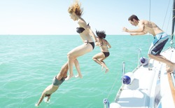 group of friends diving in the water during a boat excursion