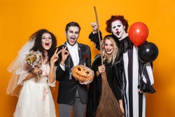 Group of friends dressed in scary costumes celebrating Halloween isolated over yellow background, holding balloons, curved pumpkin