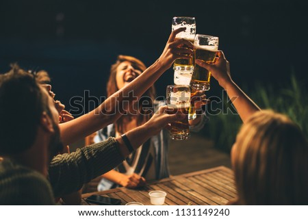 Group of friends drink beer on the terrace and toast during summer night #1131149240