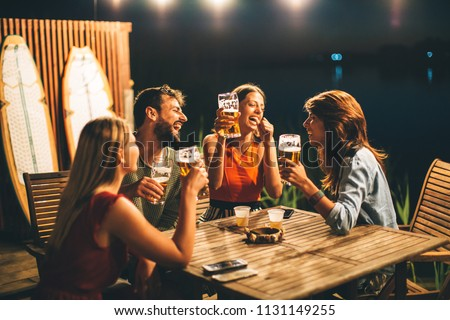 Group of friends drink beer on the terrace and toast during summer night #1131149255