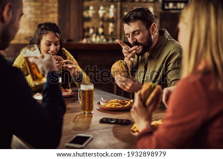 Group of friends drinking beer and eating hamburgers in a pub. Focus is on man tasting a burger.  Foto stock ©