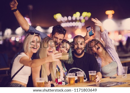 Group of friends drinking beer and taking selfie at music festival #1171803649
