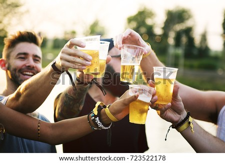 Group of Friends Drinking Beers Enjoying Music Festival Together #723522178
