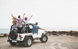 Group of friends driving off road convertible car during roadtrip - Happy travel people having fun in vacation - Friendship, transportation and youth lifestyle holidays concept