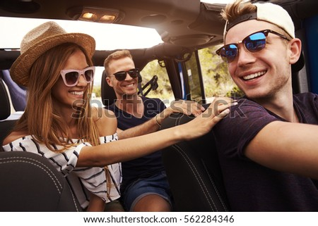 Group Of Friends Driving Open Top Car On Country Road