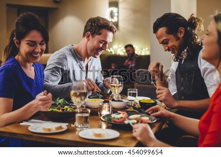 Group of friends enjoying an evening meal with wine at a restaurant.