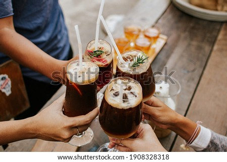 Group of friends enjoying coffe cocktail in wine glass. Creative new exotic cocktail drinks a combination of cold brew coffee with juice.