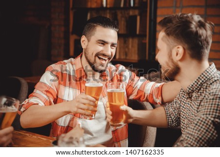 Group of friends enjoying drink pub, tells funny story.
