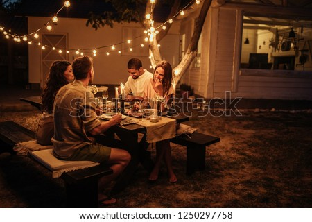 Group of friends enjoying food and drinks together outside #1250297758