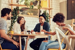 Group of friends enjoying in cafe together. Young people meeting in a cafe. Young men and women sitting at cafe table and smiling