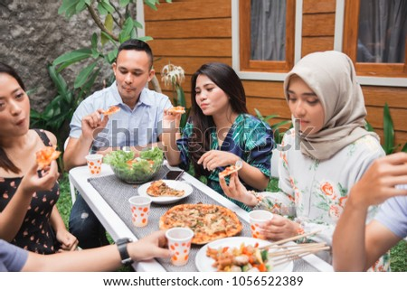 Group of friends enjoying meal at outdoor party in backyard #1056522389