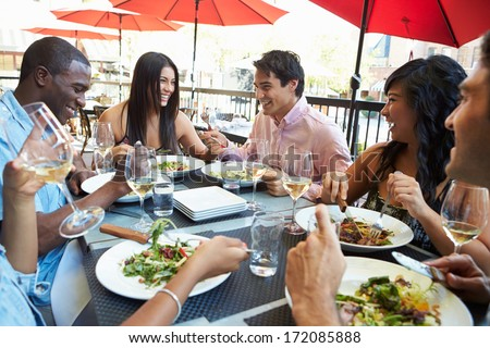 Group Of Friends Enjoying Meal At Outdoor Restaurant