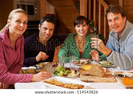Group Of Friends Enjoying Meal In Alpine Chalet Together