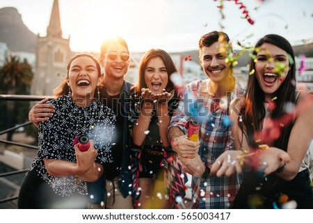 Group of friends enjoying party and throwing confetti. Friends having fun at rooftop party.