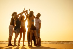 group of friends enjoying sunset in Goa India high five