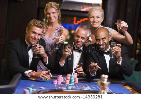 Group of friends gambling at roulette table in table