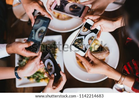 Group of friends going out and taking a photo of Italian food together with mobile phone