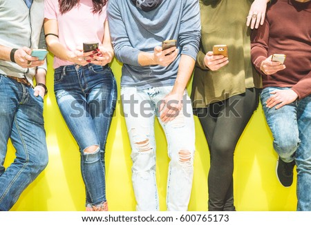 Group of friends having a social network moment watching on their mobile phones - People leaning on a yellow wall on their phones texting and taking pictures - People addicted and technology concept