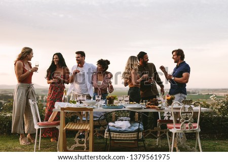 Group of friends having drinks at party in garden. Millennials enjoying dinner party outdoors. ストックフォト ©