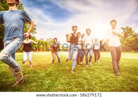 Group of friends having fun and running on green meadow