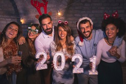 Group of friends having fun at New Years party, holding illuminative numbers 2021 representing the upcoming New Year at midnight countdown