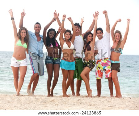 group of friends having fun at the beach with their arms up