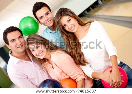 Group of friends having fun bowling and smiling