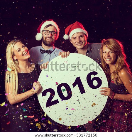 Group of friends having fun, celebrating New Year\'s Eve and holding cardboard circle with 2016 written on it